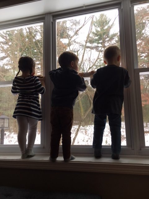 Children looking out window in awe